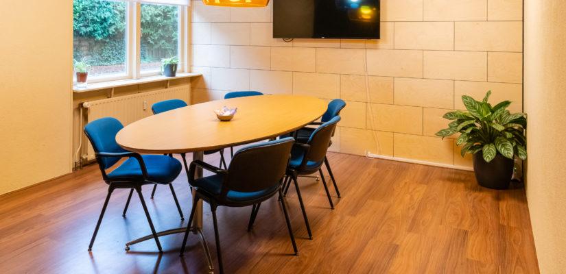 De achterkamer heeft een grote ovalen tafel, acht stoelen en een beeldscherm.